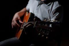 Homme jouant une guitare acoustique sur un fond foncé Jeu de la guitare photos stock