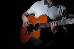 Homme jouant une guitare acoustique sur un fond foncé Jeu de la guitare photo libre de droits