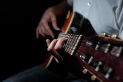 Homme jouant une guitare acoustique sur un fond foncé Jeu de la guitare image libre de droits