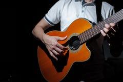 Homme jouant une guitare acoustique sur un fond foncé Jeu de la guitare photos libres de droits