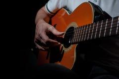 Homme jouant une guitare acoustique sur un fond foncé Jeu de la guitare photographie stock libre de droits
