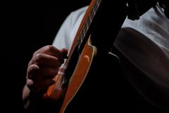 Homme jouant une guitare acoustique sur un fond foncé Jeu de la guitare images stock