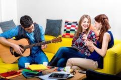 Homme jouant une guitare avec des amies Photographie stock