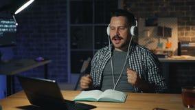 Homme joyeux appréciant la musique dans des écouteurs occupés avec la danse d'ordinateur portable dans le bureau foncé banque de vidéos