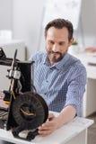 Homme joyeux avec plaisir travaillant dans son bureau Images stock