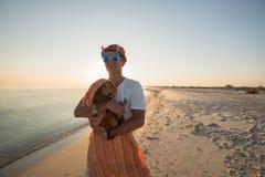 Homme joyeux dans lunettes de soleil drôles avec un petit chien Photos libres de droits