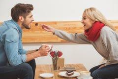 Homme joyeux et femme prenant le petit déjeuner en café Photos stock