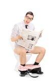 Homme joyeux lisant les actualités posées sur une toilette Photo stock