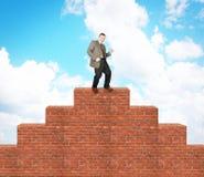 Homme joyeux monté sur la pyramide de brique Photo libre de droits