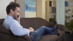 Homme joyeux parlant sur le téléphone portable et la conversation et la relaxation souriantes et gentilles banque de vidéos