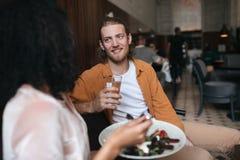 Homme joyeux s'asseyant dans le restaurant et parlant avec la fille Garçon de sourire s'asseyant au café avec le verre de l'eau à Photographie stock