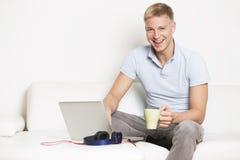 Homme joyeux s'asseyant sur le divan avec l'ordinateur portable et le café potable. image stock