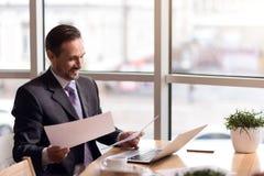 Homme joyeux travaillant avec le papier Photos libres de droits