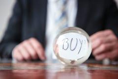 Homme jugeant de papier avec l'achat de mot devant la boule en verre Images stock