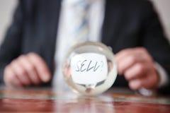 Homme jugeant de papier avec la vente de mot devant la boule en verre Photos libres de droits