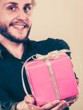 Homme jugeant le boîte-cadeau rose actuel disponible Photo libre de droits