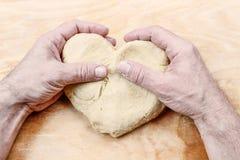 Homme jugeant le coeur fait de pâtisserie photographie stock