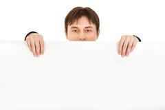 Homme jugeant le panneau-réclame blanc d'isolement Photographie stock