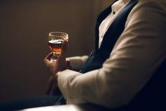 Homme jugeant le whiskey en verre dans des mains Photos libres de droits