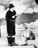 Homme jugeant une canne à pêche et une jeune femme s'asseyant devant lui avec une cuvette (toutes les personnes représentées ne s Images libres de droits
