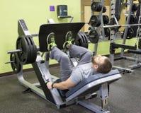 Homme à l'aide de la presse de jambe chargée par plat Image stock
