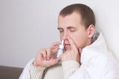 Homme à l'aide de la pulvérisation nasale dans son salon Image libre de droits