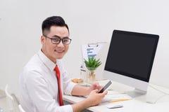 Homme ? l'aide de l'ordinateur et du t?l?phone intelligent ? la table dans le bureau contre la fen?tre images stock