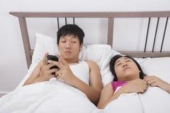Homme à l'aide du téléphone portable tout en regardant la femme dormant dans le lit Image stock