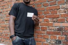 Homme ? la peau fonc?e dans le T-shirt montrant la carte de visite professionnelle vierge de visite sur le fond bricked photographie stock libre de droits