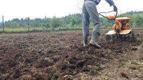 Homme labourant le champ avec le cultivateur banque de vidéos