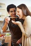 Homme laissant le femme goûter le potage Photo stock