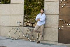 Homme latin attirant heureux dans l'équitation gaie de sourire de vêtements à la mode occasionnels sur bicyclette fraîche de vint Photo stock