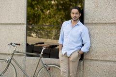 Homme latin attirant heureux dans l'équitation gaie de sourire de vêtements à la mode occasionnels sur bicyclette fraîche de vint Photos stock