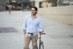 Homme latin attirant heureux dans l'équitation gaie de sourire de vêtements à la mode occasionnels sur bicyclette fraîche de vint Photographie stock