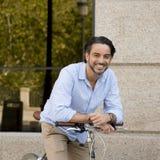 Homme latin attirant heureux dans l'équitation gaie de sourire de vêtements à la mode occasionnels sur bicyclette fraîche de vint Photographie stock libre de droits