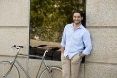Homme latin attirant heureux dans l'équitation gaie de sourire de vêtements à la mode occasionnels sur bicyclette fraîche de vint Photo libre de droits