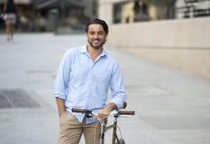 Homme latin attirant heureux dans l'équitation gaie de sourire de vêtements à la mode occasionnels sur bicyclette fraîche de vint Image stock