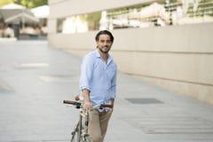 Homme latin attirant heureux dans l'équitation gaie de sourire de vêtements à la mode occasionnels sur bicyclette fraîche de vint Image libre de droits