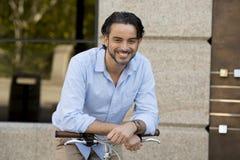Homme latin attirant heureux dans l'équitation gaie de sourire de vêtements à la mode occasionnels sur bicyclette fraîche de vint Images libres de droits