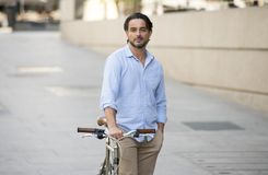 Homme latin attirant heureux dans l'équitation gaie de sourire de vêtements à la mode occasionnels sur bicyclette fraîche de vint Photos libres de droits