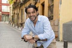 Homme latin attirant heureux dans l'équitation gaie de sourire de vêtements à la mode occasionnels sur bicyclette fraîche de vint Images stock