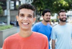 Homme latin riant avec deux amis dans la ville Photographie stock libre de droits