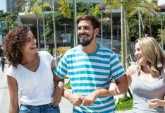 Homme latin riant avec l'amie caucasienne de femme et d'hispanique Photographie stock libre de droits