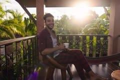 Homme latin s'asseyant sur le sourire heureux de tasse de prise de terrasse d'été, Guy In Morning Drinking Coffee dehors photos libres de droits