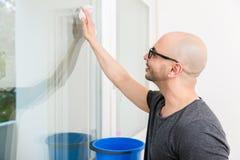 Homme lavant le verre de fenêtre avec le tissu images stock