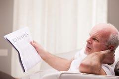 Homme lisant un journal sur un sofa Image libre de droits