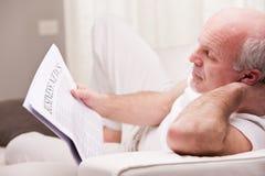Homme lisant un journal sur un sofa Photo stock
