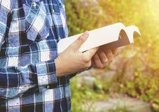Homme lisant un livre en parc Étudiant étudiant mémorisant des notes dehors Images stock