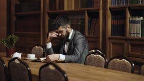 Homme lisant un livre pendant la pause-caf? L'homme dans le costume classique s'assied dans l'intérieur de cru, bibliothèque, éta banque de vidéos