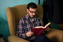 Homme lisant un livre sur le sofa dans sa maison image stock